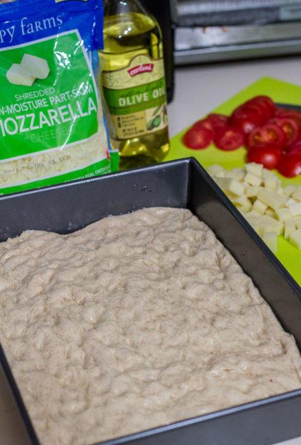 risen pizza dough in the baking pan