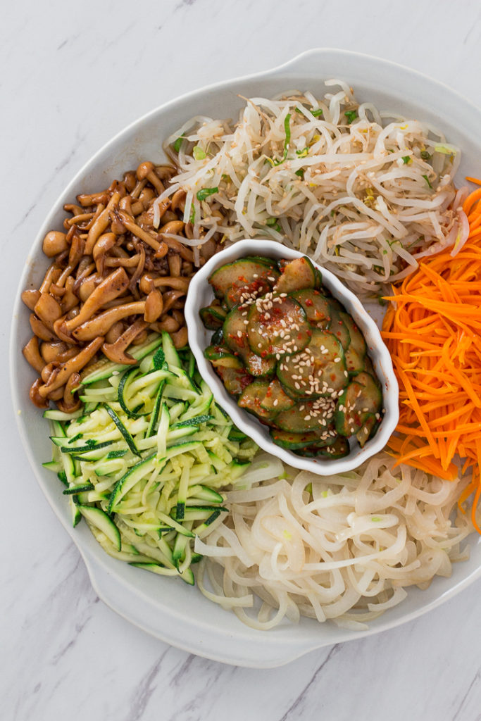 Ingredients for bibimbap - bean sprouts, carrot, onion, zucchini, mushroom, and cucumber kimchi
