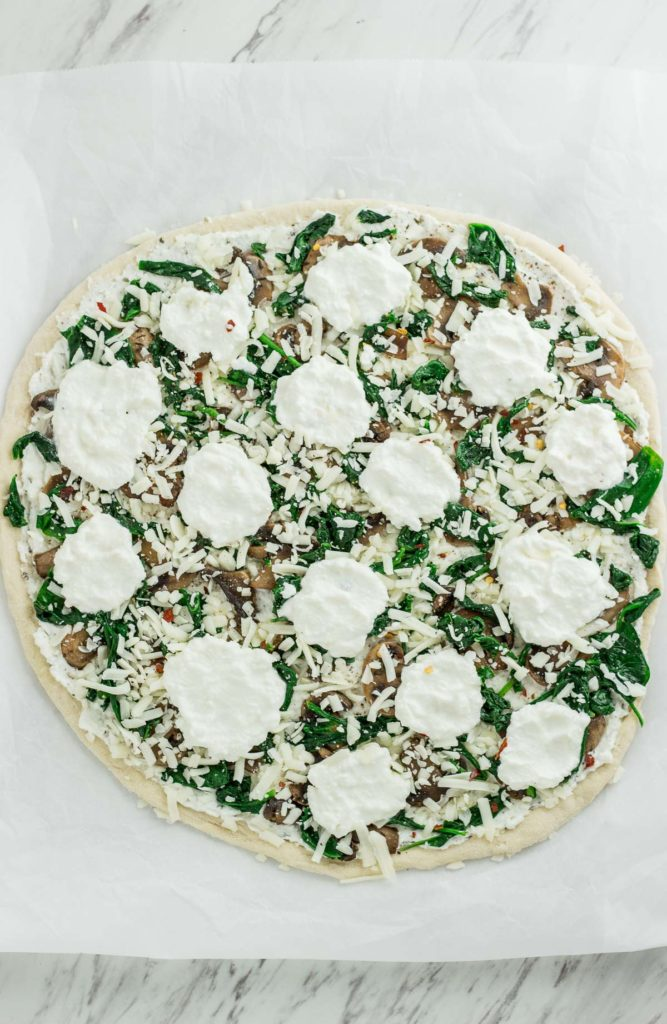 Whole white pizza with extra dollops of ricotta cheese on top, before baking in the oven