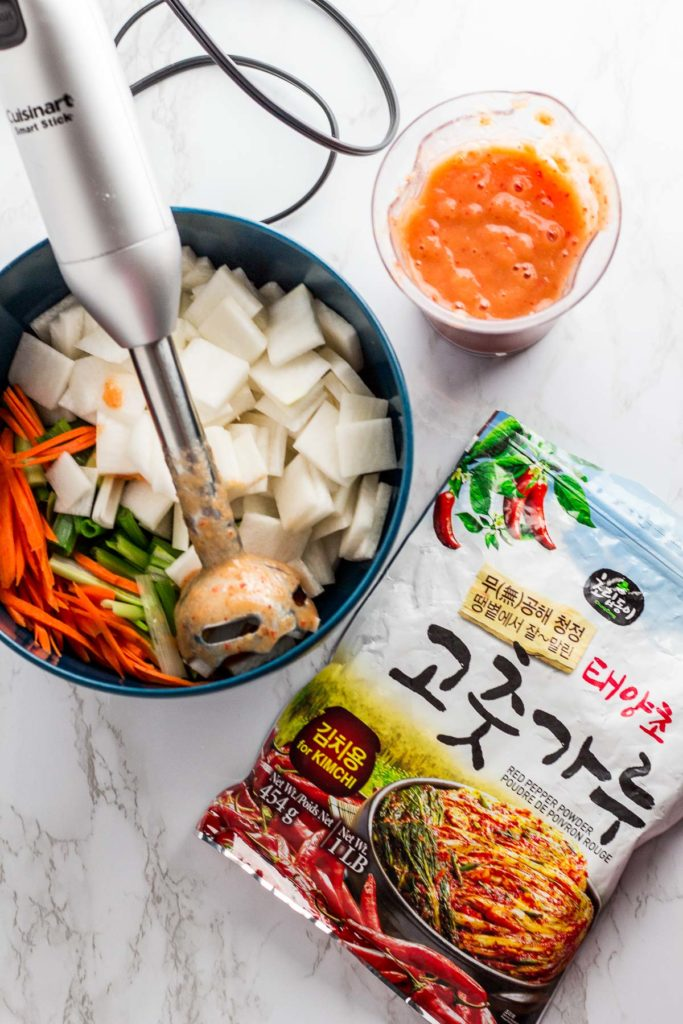 Ground up sauce with prepared vegetables for the kimchi in a bowl and a bag of korean red pepper flakes on the side