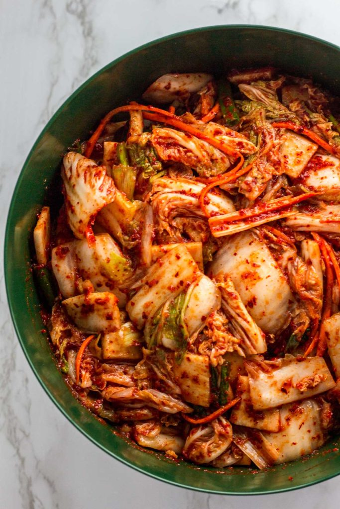 salted napa cabbage and vegetable with the sauce mixed in in a big bowl