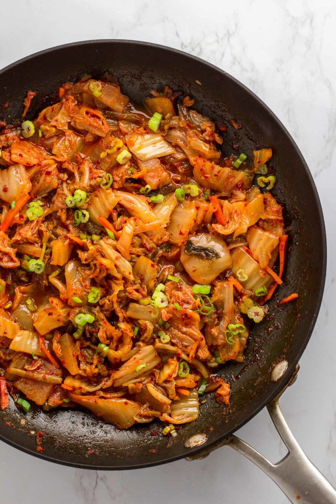 chopped kimchi in frying pan with green onion garnish on top
