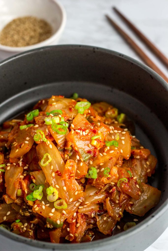 Close up picture of stir fried kimchi in a black bowl