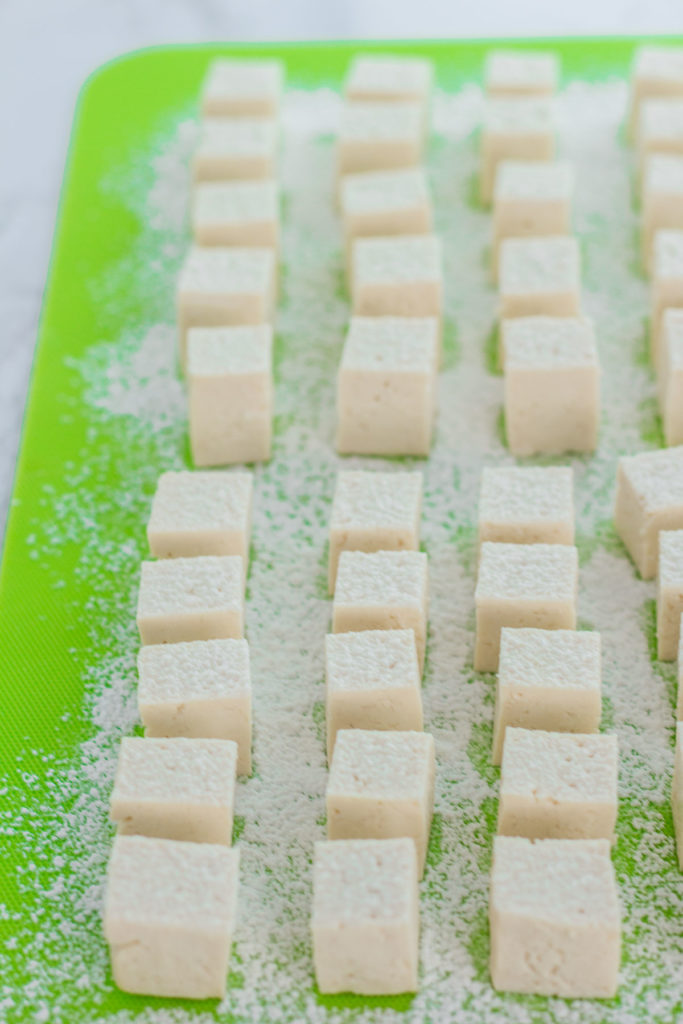 Tofu cubes on the cutting board with corn starch dusted on top