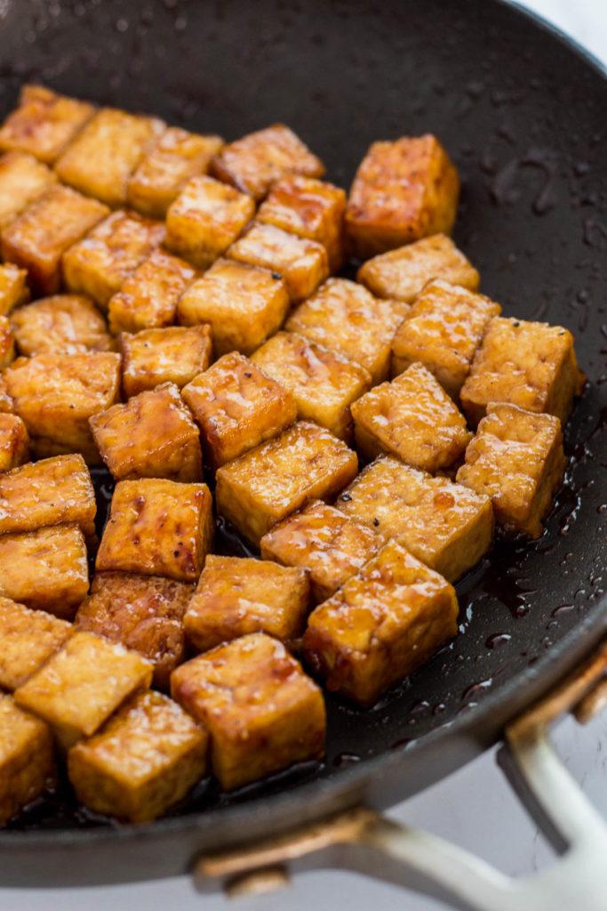 close up photo of vegan teriyaki pan-fried tofu in the pan
