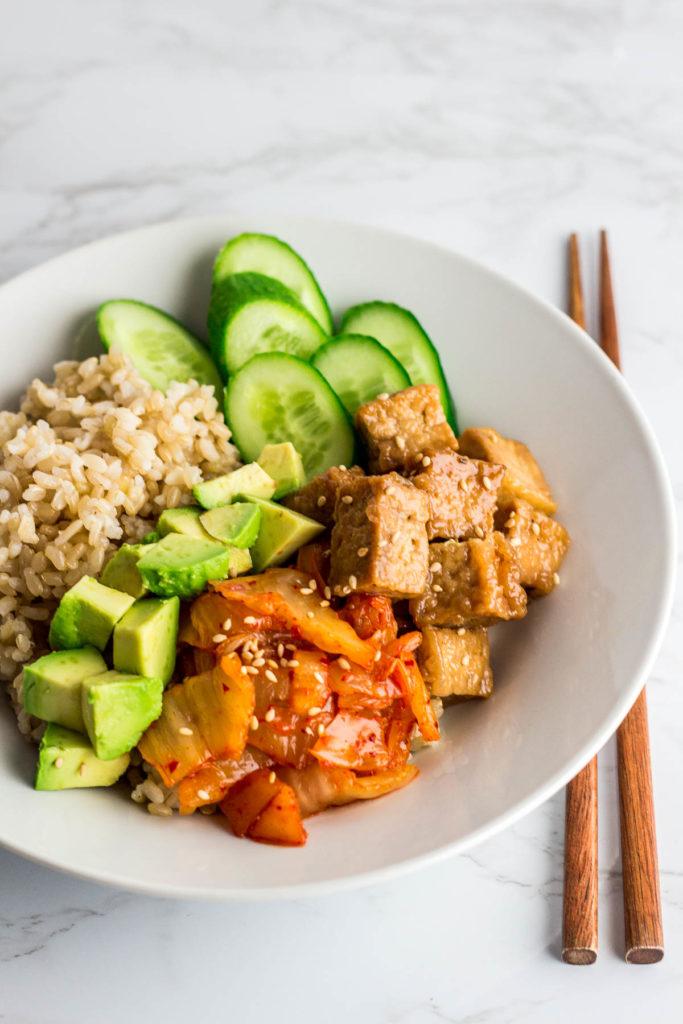 vegan teriyaki pan-fried tofu buddha bowl with stir fried kimchi, avocado, and cucumber over brown rice