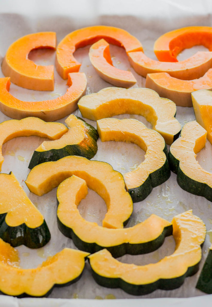 Acorn squash and butternut squash on a baking pan before baking