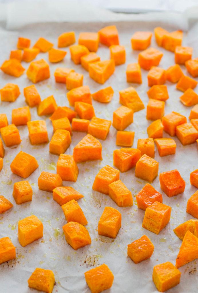 Baked butternut squash cubes on a baking sheet