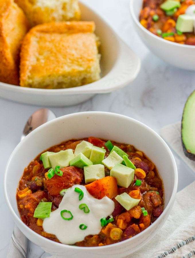 two bowls of winter squash chili with corn bread on the side