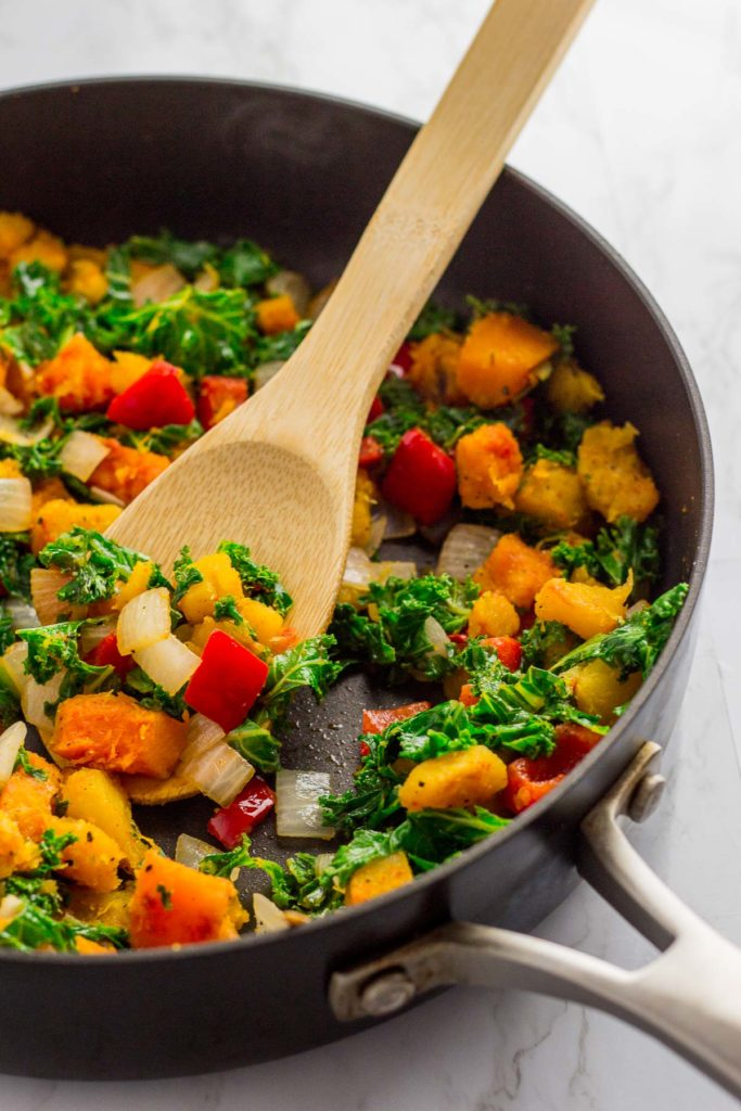 45 degree angel photo of cooked winter squash kale hash with spatula in the pan