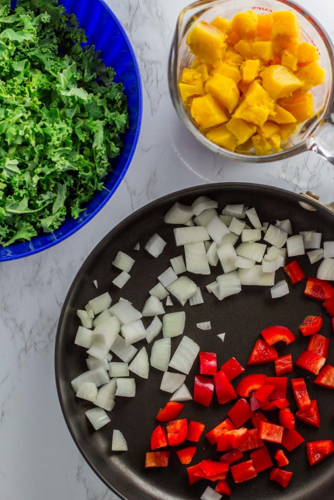 A photo of kale, baked winter squash, and onion and red bell pepper in the pan