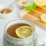 photo of tea with lemon slice on top and have lemon and honey in the background