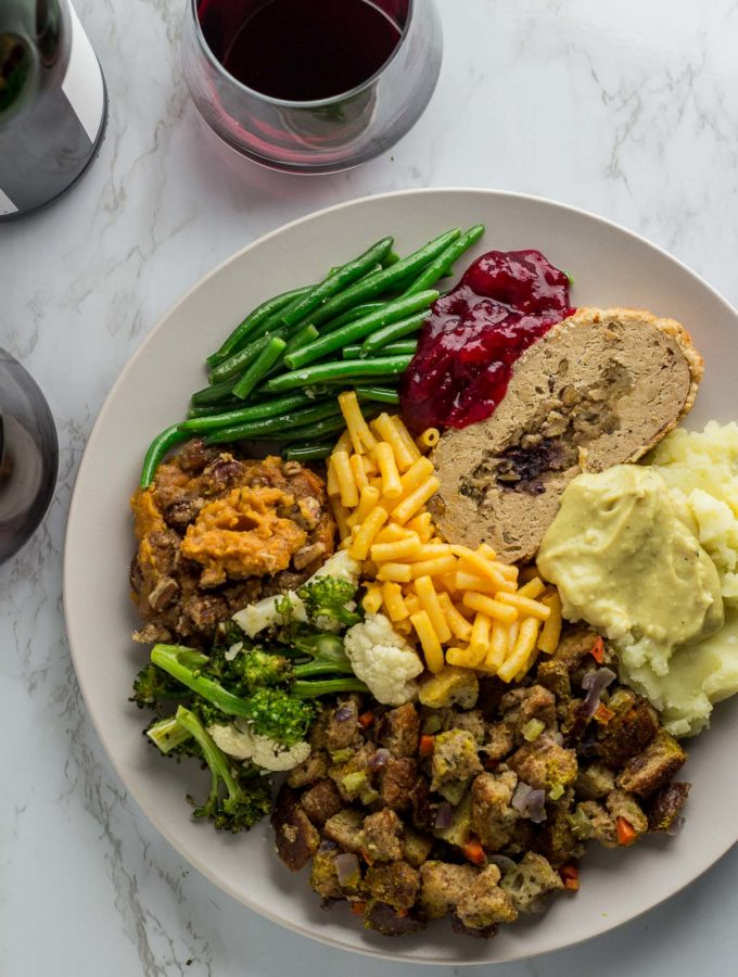 Vegetarian thanksgiving dinner plate - green bean, cranberry sauce, vegan turkey, mac and cheese, mashed potato, stuffing, and roasted broccoli and cauliflower