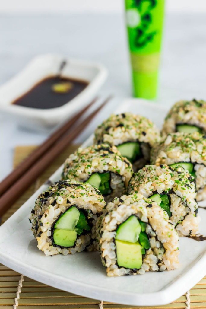 Close up shot of inside out vegan green sushi roll. The rolls are placed on top of rectangular plate with soy sauce in the back ground.