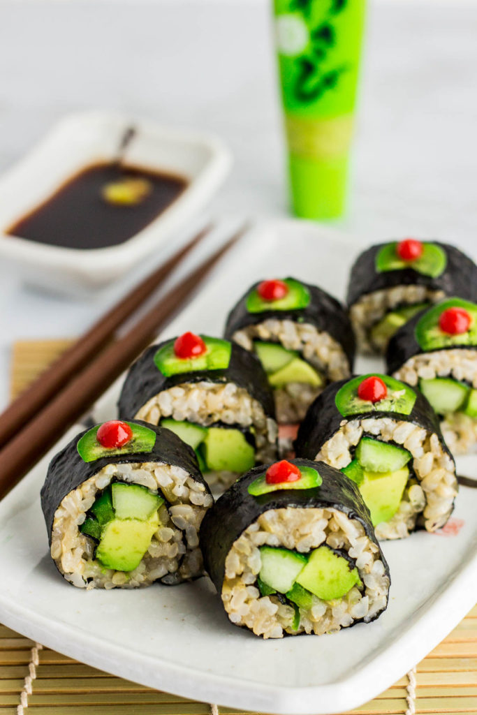 Close up shot of regular vegan green sushi roll (vegan uramaki). It is decorated with thin slice of jalapeno dotted with sriracha sauce on top of each roll.