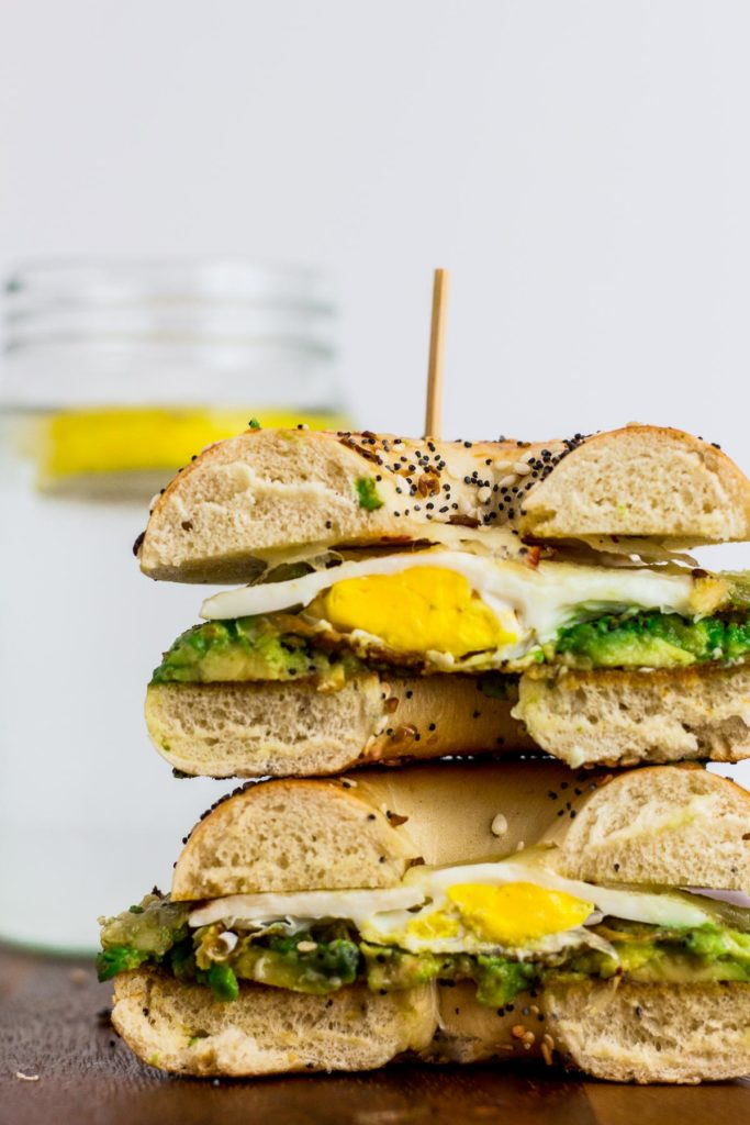 Cross cut of bagel sandwich, can see mashed avocado and fried egg