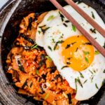 A black bowl full of kimchi fried rice with fried egg on top