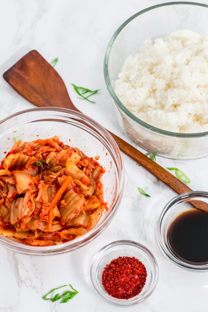 Ingredients to make fried rice - rice, kimchi, red pepper flakes, soy sauce