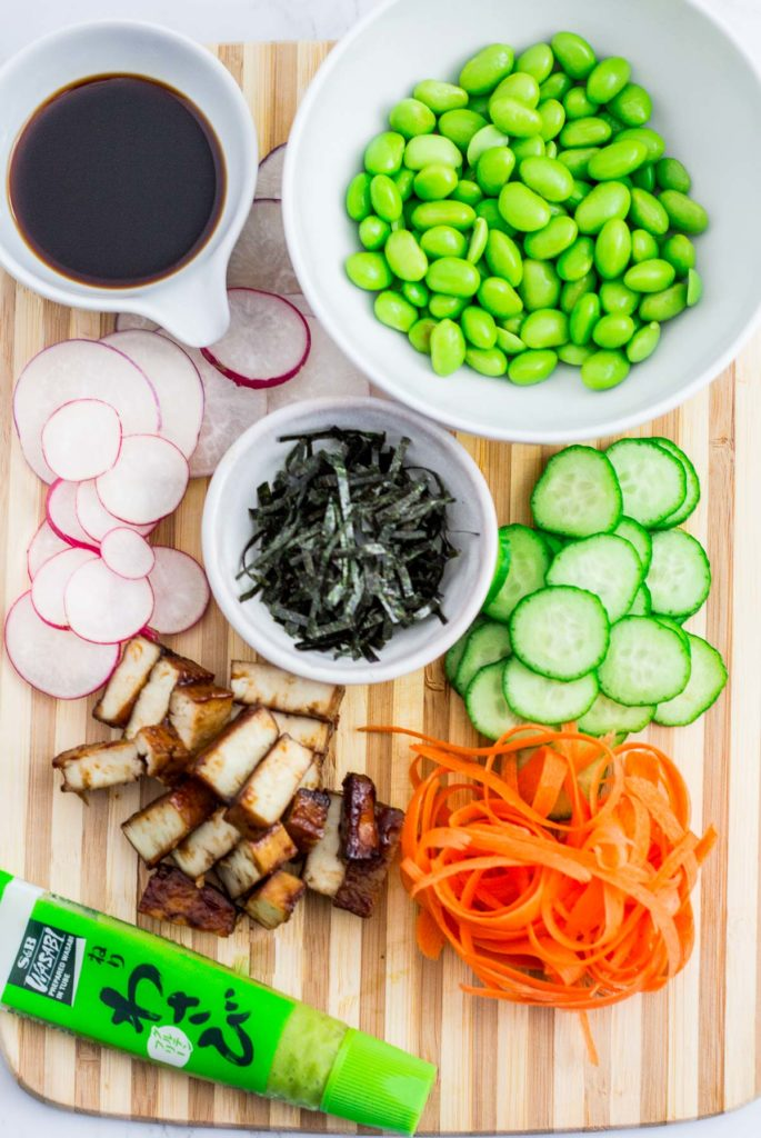 over head shot of all the ingredients to make the sushi bowl - hoisin tofu, carrots, cucumber, radish, edamame, soy sauce, seaweed flakes and wasabi