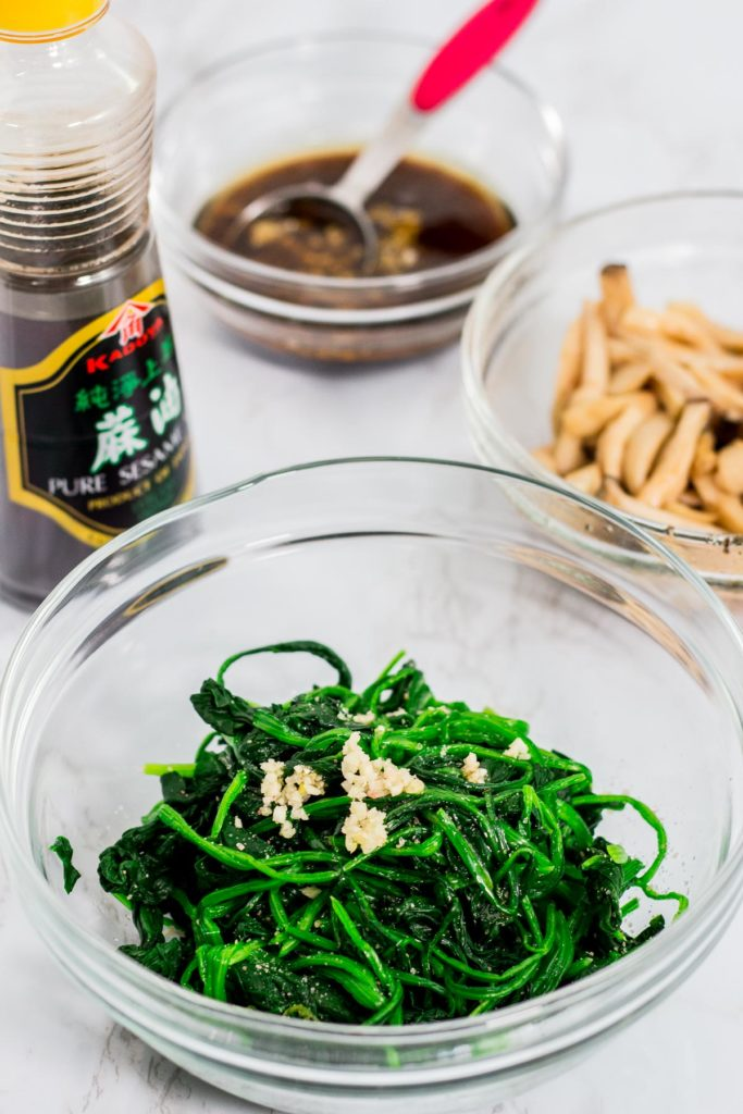 A clear bowl of blenched spinach with salt, minced garlic, and sesame oil and japchae sauce in the background along with mushroom
