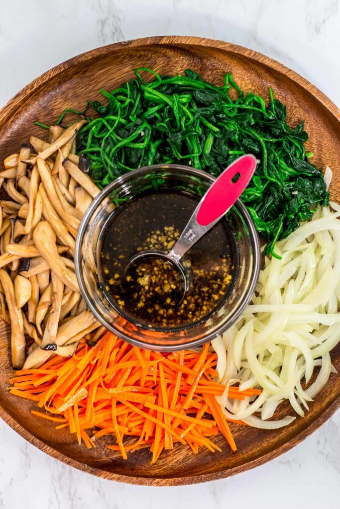Ingredients to make japchae - blenched spinach, sauteed onion and carrots, and stir fried king oystered mushroom with sauce in the middle