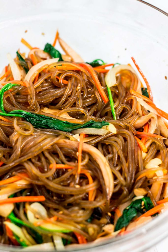 In the process of mixing japchae in a large bowl