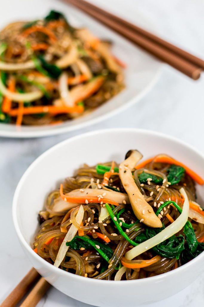 Two bowls of Korean vegan japchae with chopsticks next to them