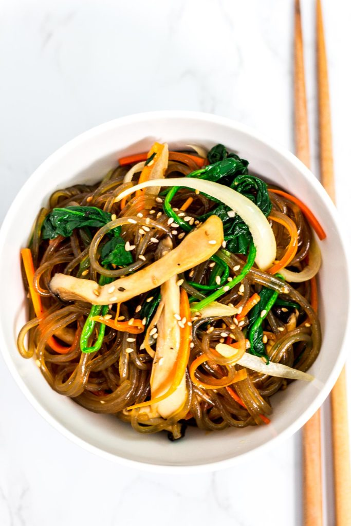Overhead shot of Korean vegan japchae in a white bowl with chopsticks next to it