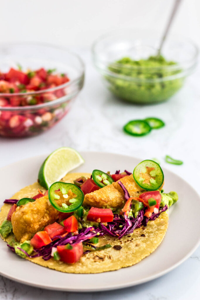 a vegetarian/vegan fish stick tacos on a plate with salsa and guacamole in the background