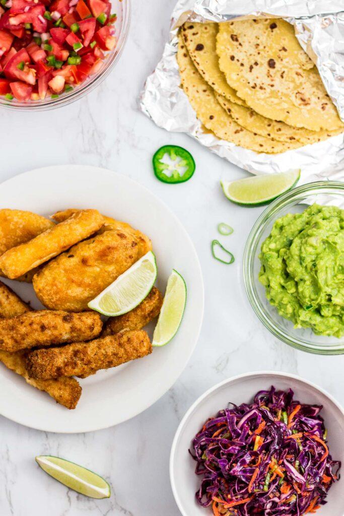 a bowl of salsa, corn tortilla, guacamole, purple cabbage slaw, and fish sticks