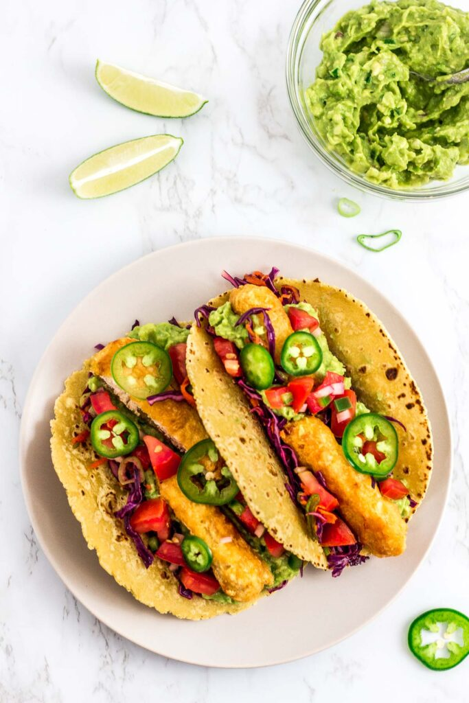 two prepared vegan fish stick tacos on a plate with guacamole in the background