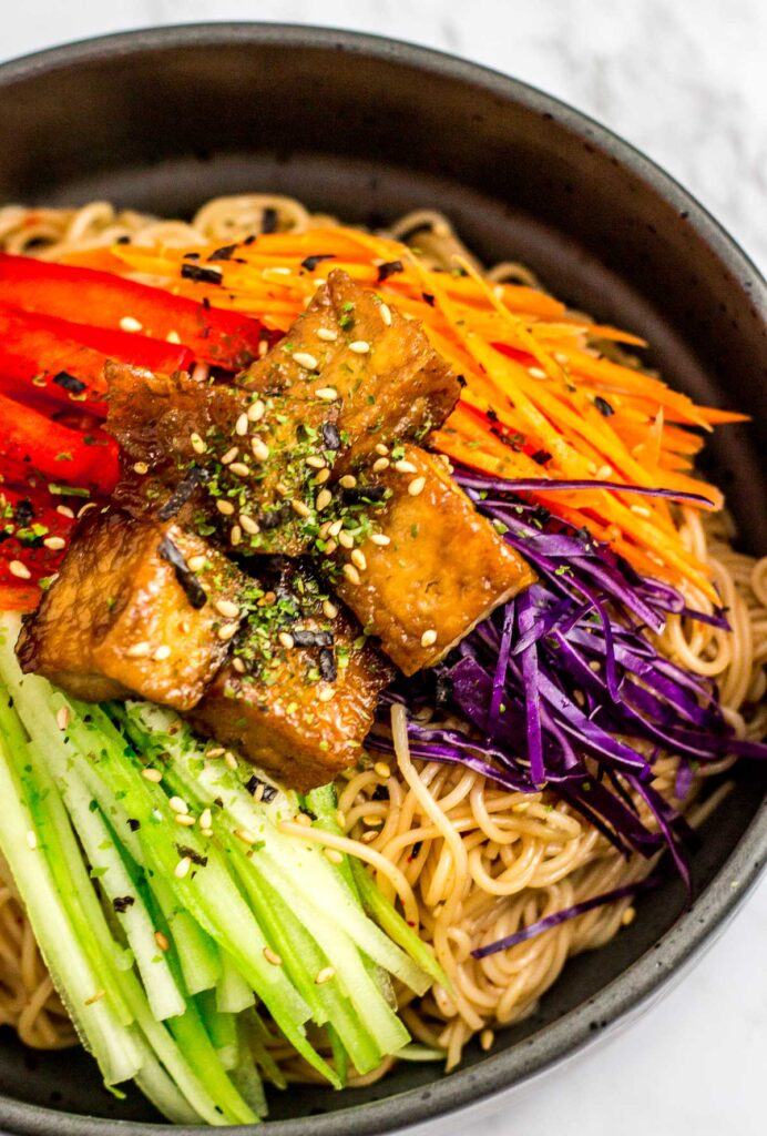 Close up shot of a bowl of Korean noodle salad with soy sauce