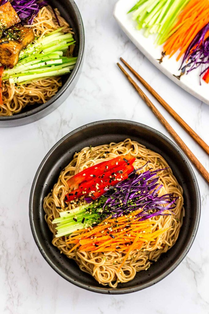 overhead shot of two bowls of Korean noodle salad with soy sauce with vegetables on the side