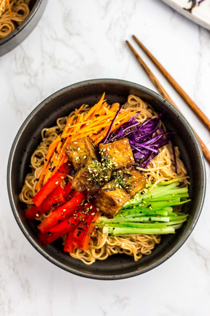 noodle salad in the black bowl with different vegetables and teriyaki tofu on top