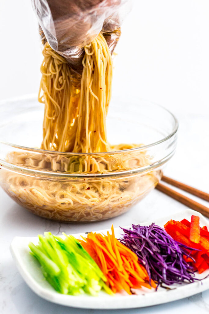 mixing somen noodle with the sauce, vegetable toppings are on the plate in front