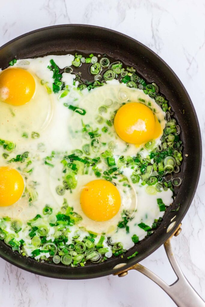 4 fried eggs with sauteed green onion in a large pan
