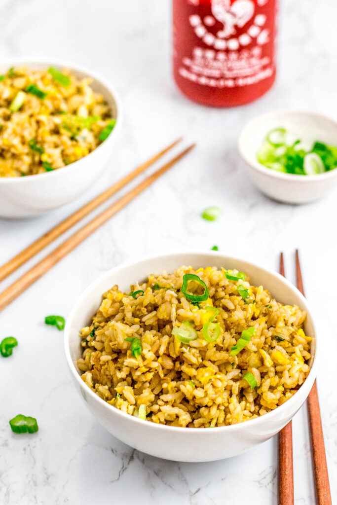 two bowls of super easy 5 ingredients egg fried rice with sriracha and green onion on the side
