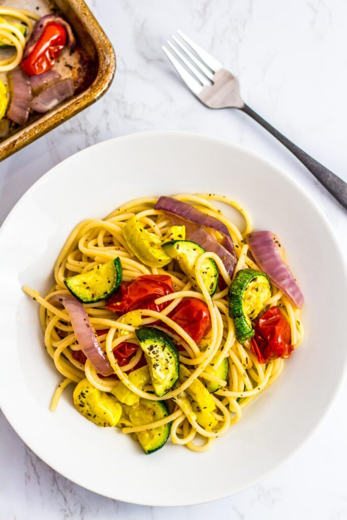 a white plate full of oven roasted summer veggie pasta with fork on the side