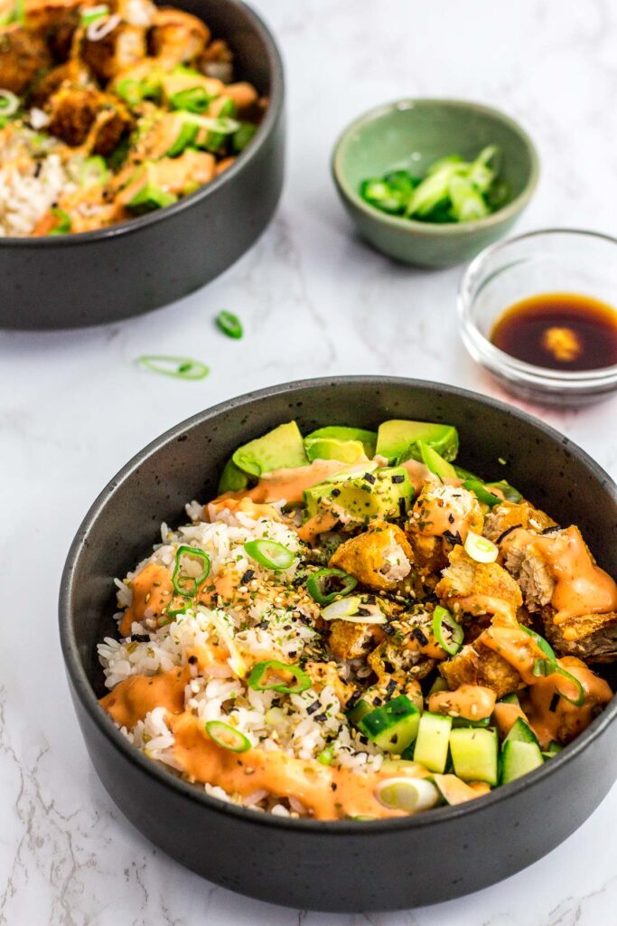 two vegan fish sticks sushi bowls with spicy mayo on top