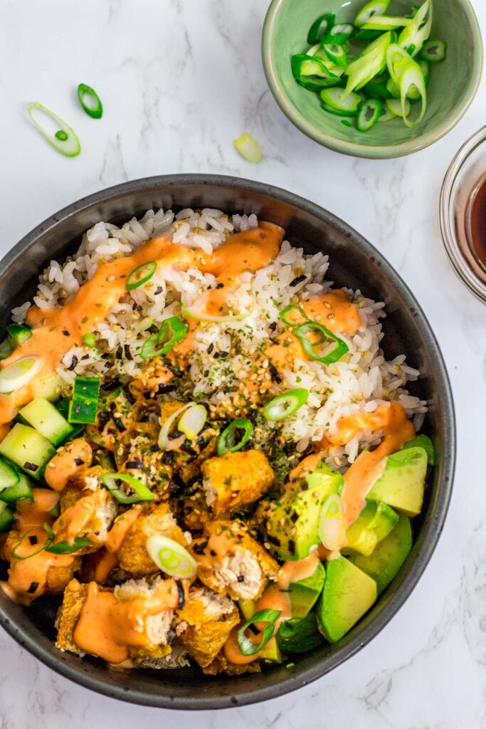 overhead shot of vegan sushi bowl with rice, vegan fish filets, avocado, cucumber