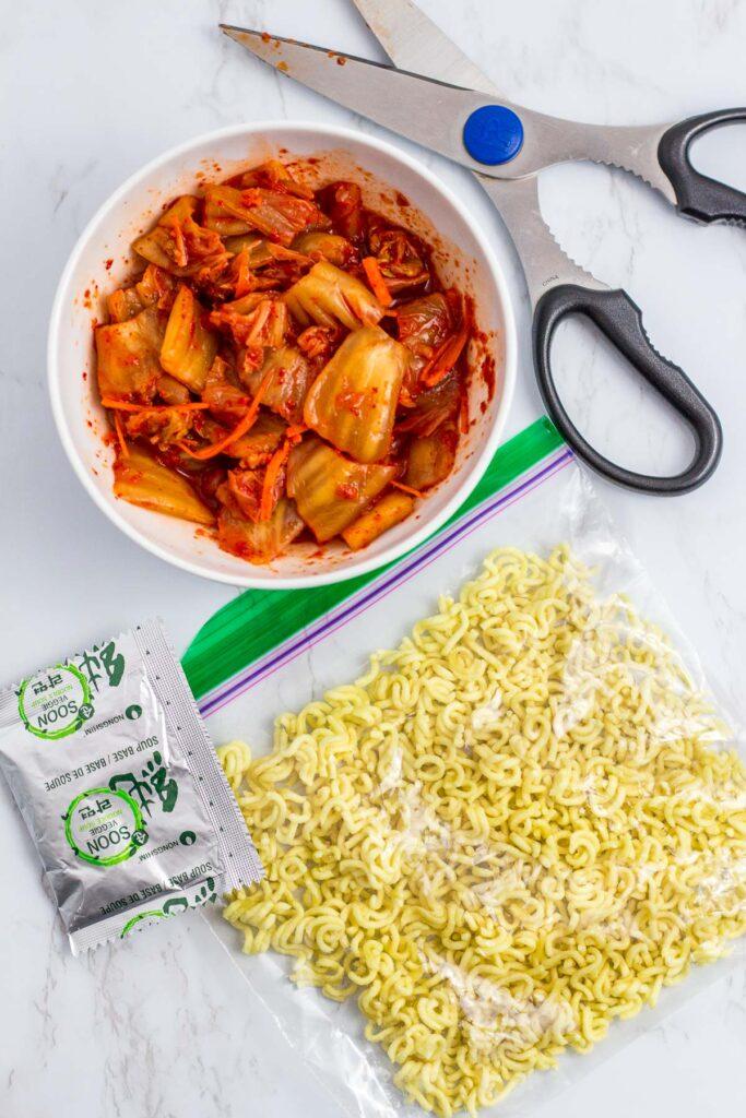 Overhead shot of vegan kimchi and broken ramen in the zip lock bag