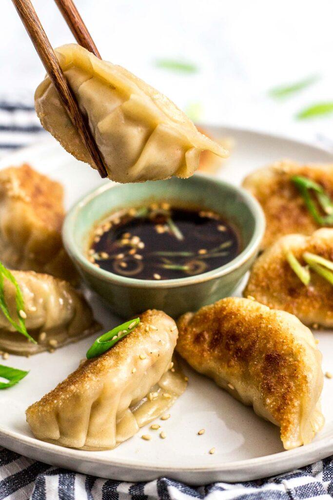 Holding a pan fried Homemade Korean Veggie Tofu Mandu/dumpling with chopsticks from a plate