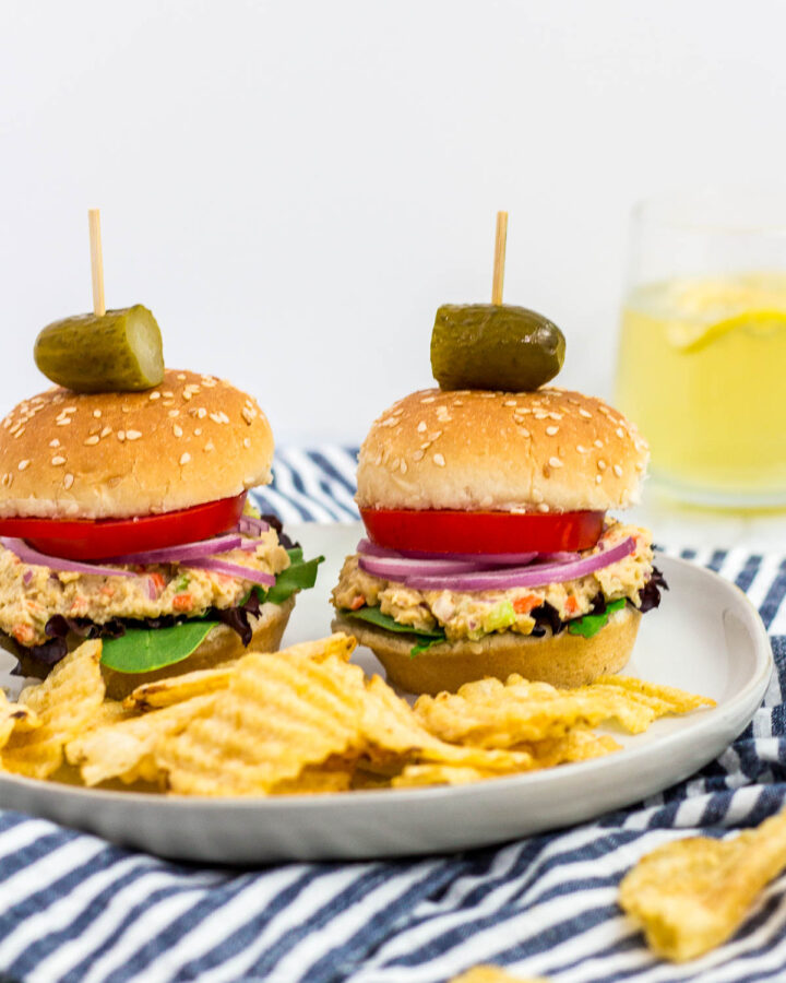 two mini canned chickpea salad sandwiches on a plate with some potato chips