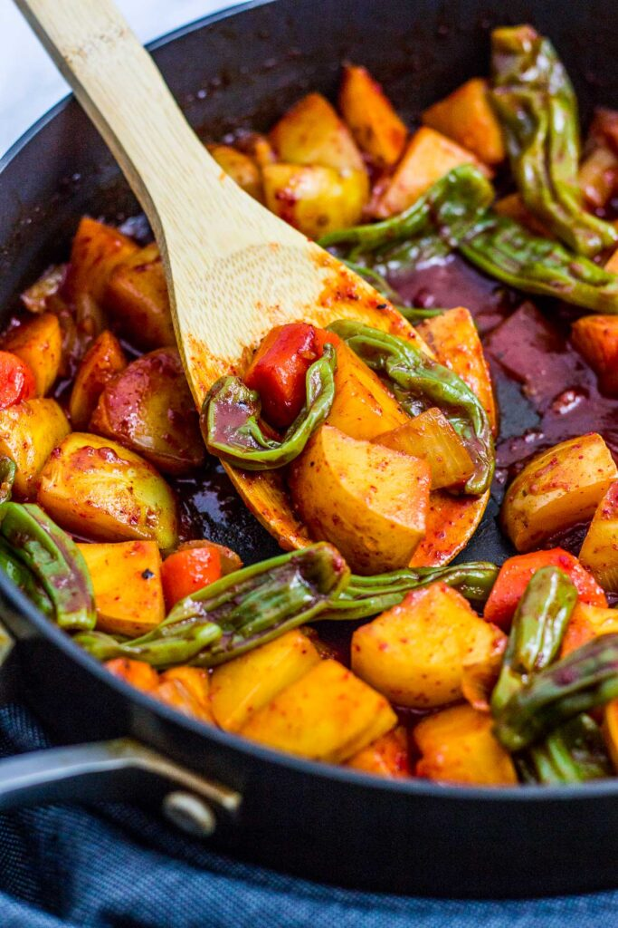braised potato and shishito peppers in the skillet with a wooden spoon
