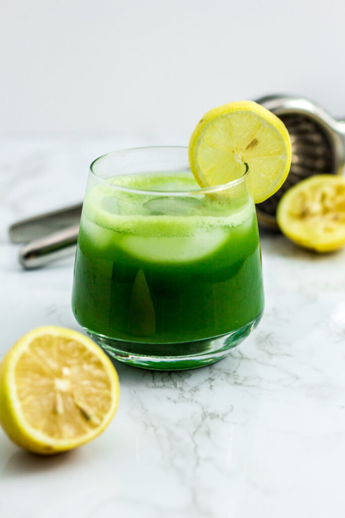 iced matcha lemonade with lemon and citrus squeezer in the background