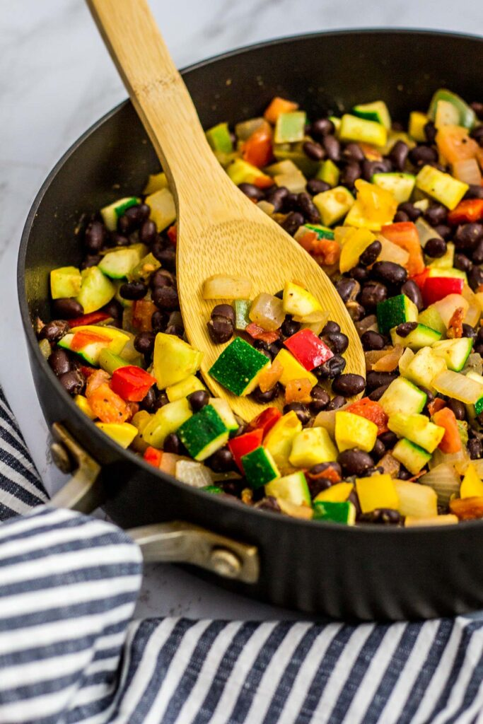 zucchini, yellow squash, tomato, onion, bell pepper and black beans in the pan