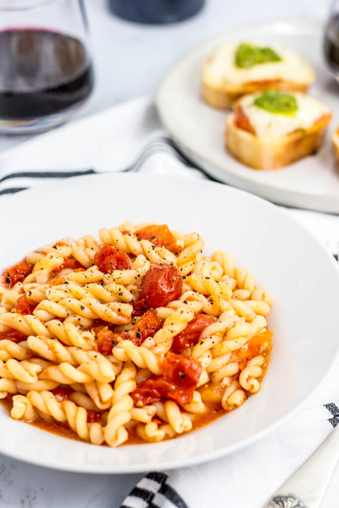 pasta with slow roasted cherry tomatoes and crostini in the background