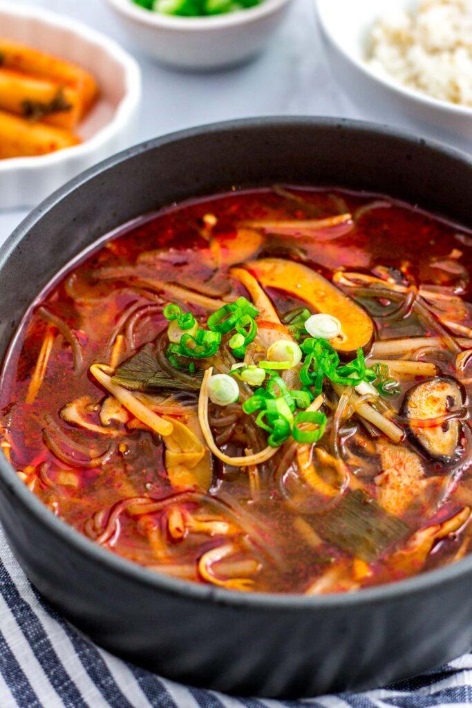 Big bowl of vegan mushroom yukgaejang with green onion garnish on top