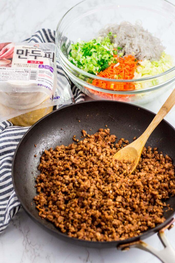 vegan beefless ground seasoned with bulgogi sauce, vegetables, Korean sweet potato noodles, and dumpling wrappers