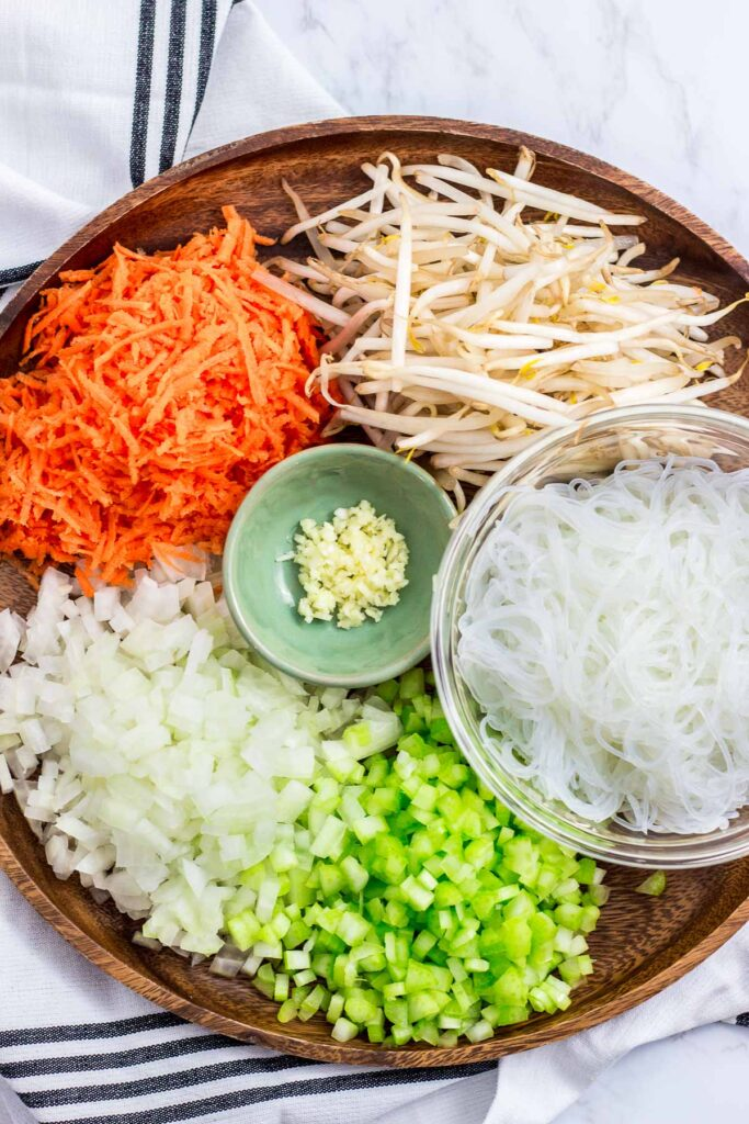 ingredients for vegan lumpia - bean sprouts, grated carrot, minced onion and celery, minced garlic, and vermicelli noodle